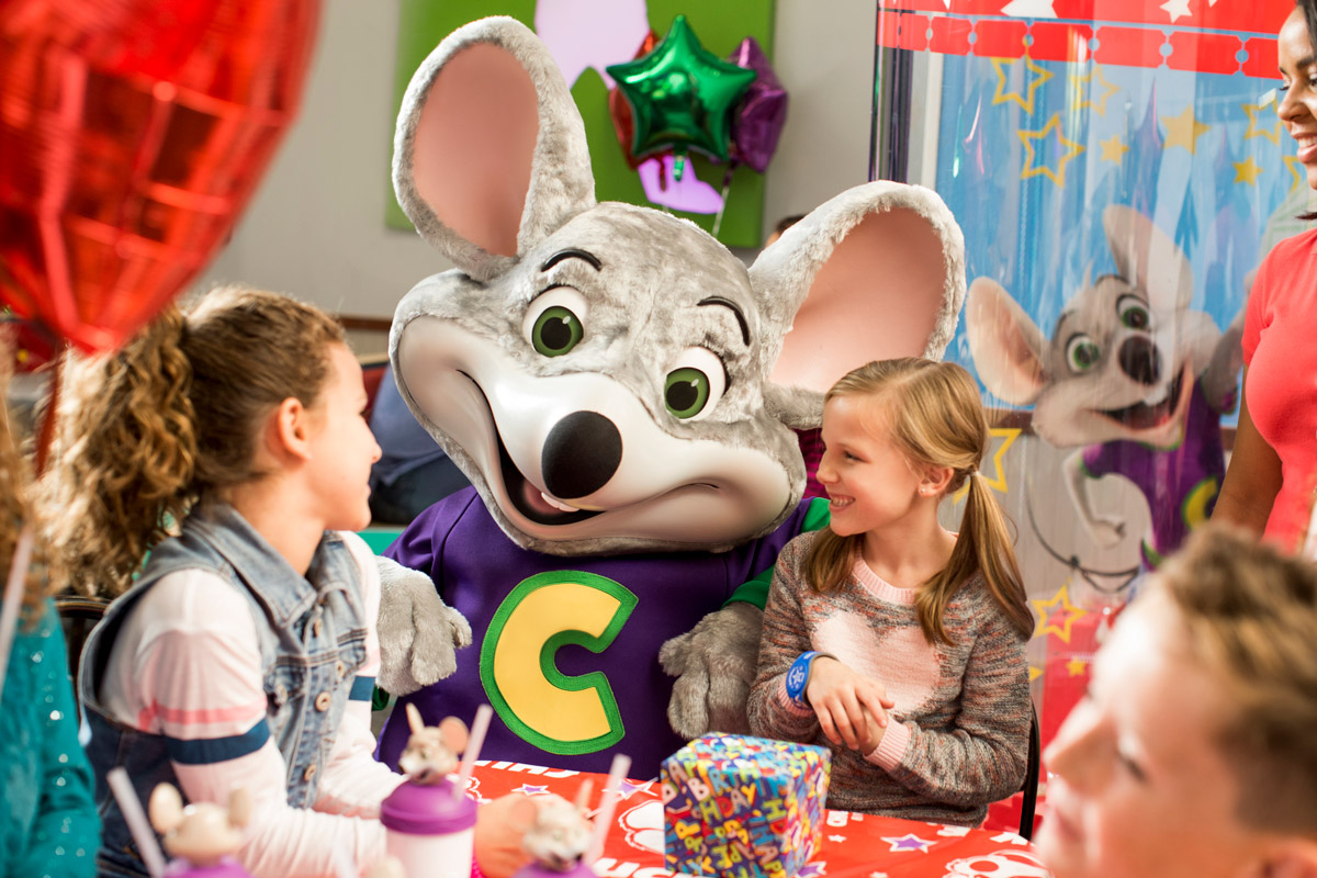 Chuck E. visiting with kids at table