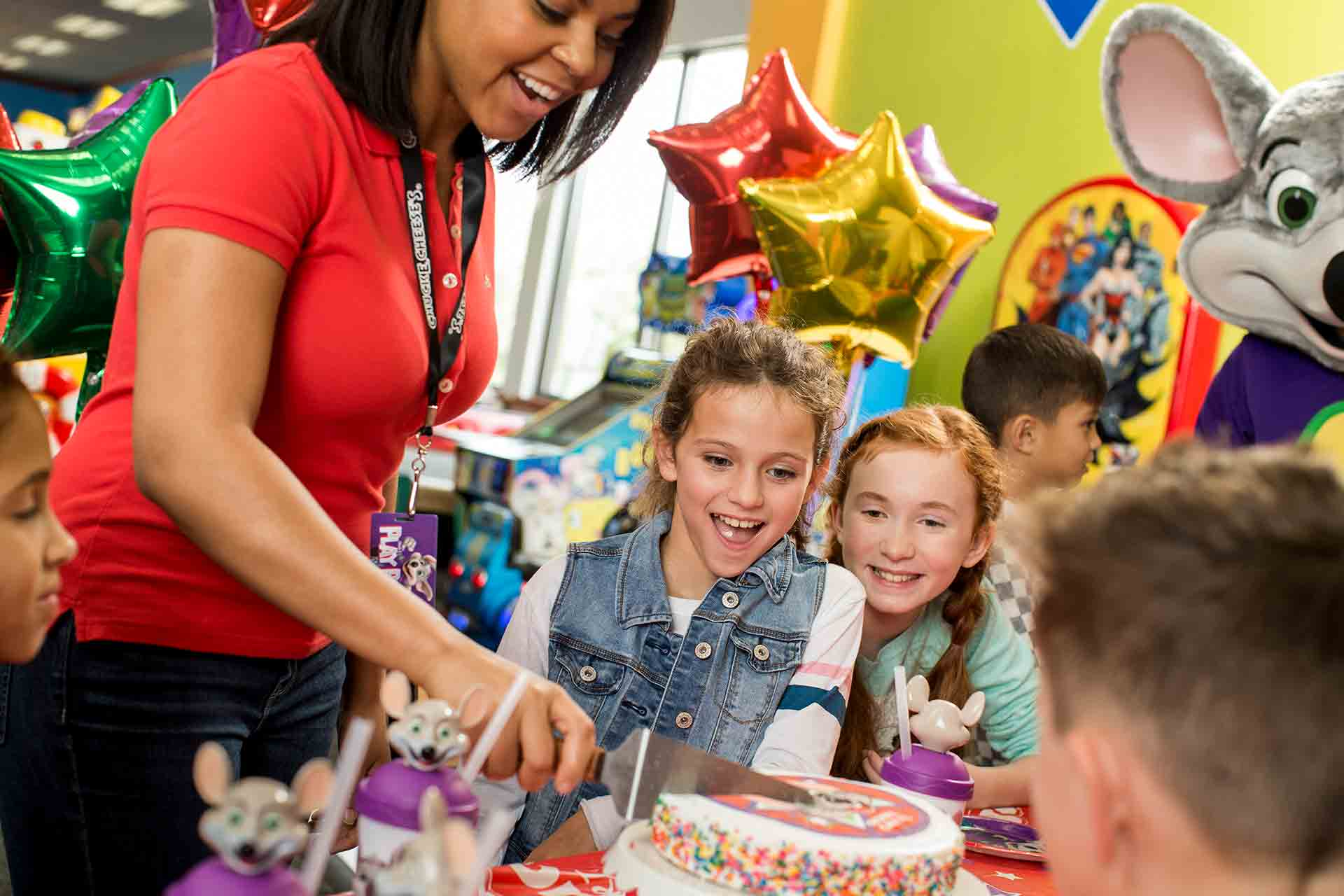 Employee cutting cake for kids