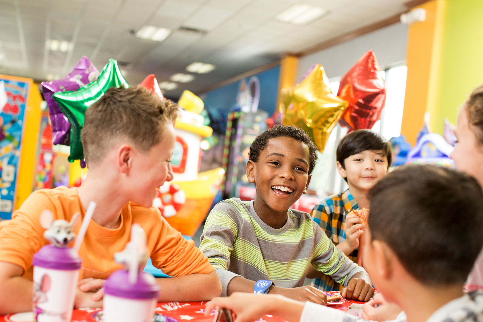 Kids around a table with balloons in the background