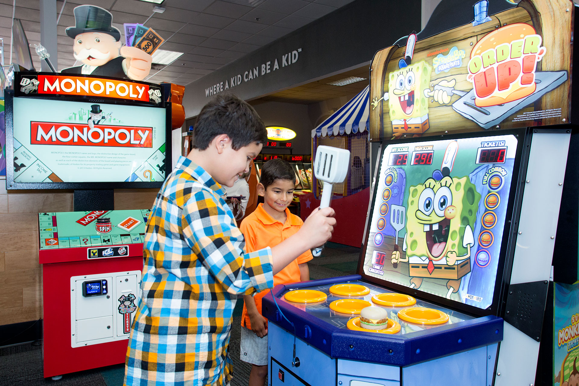 Two kids playing arcade game