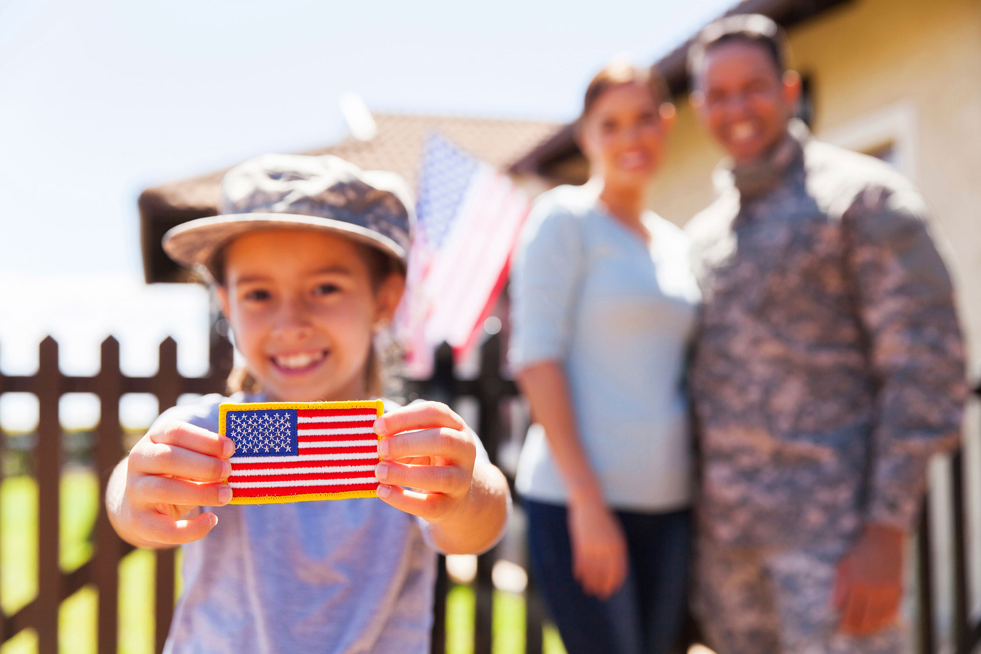 Child holding American flag patch with parents in background