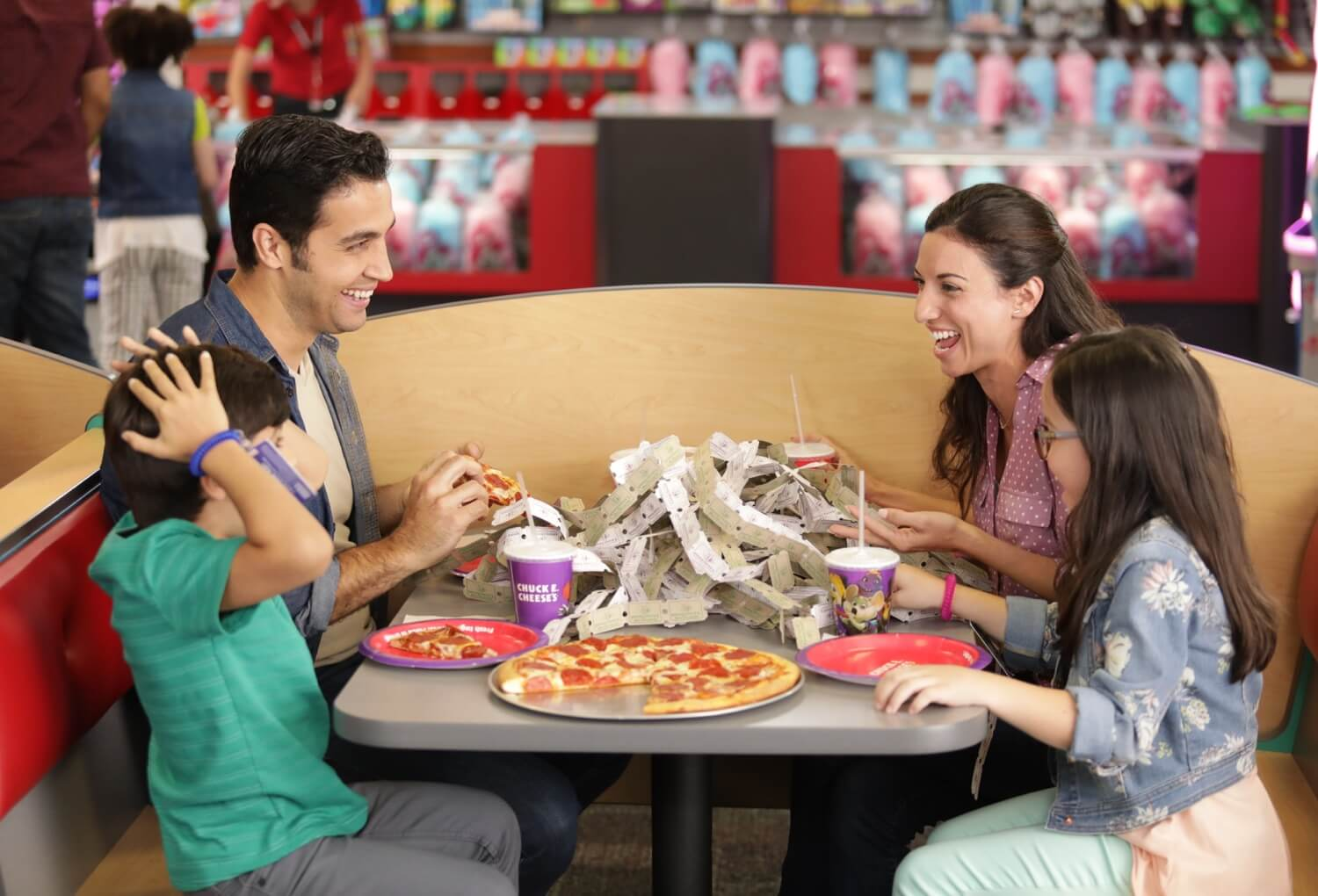 Family eating dinner with pizza and tickets on table