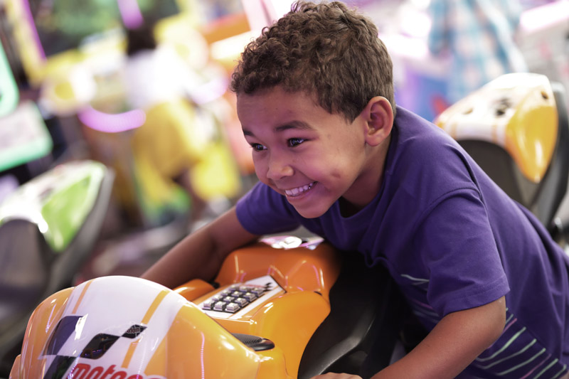 Kid smiling while riding motorcycle arcade game