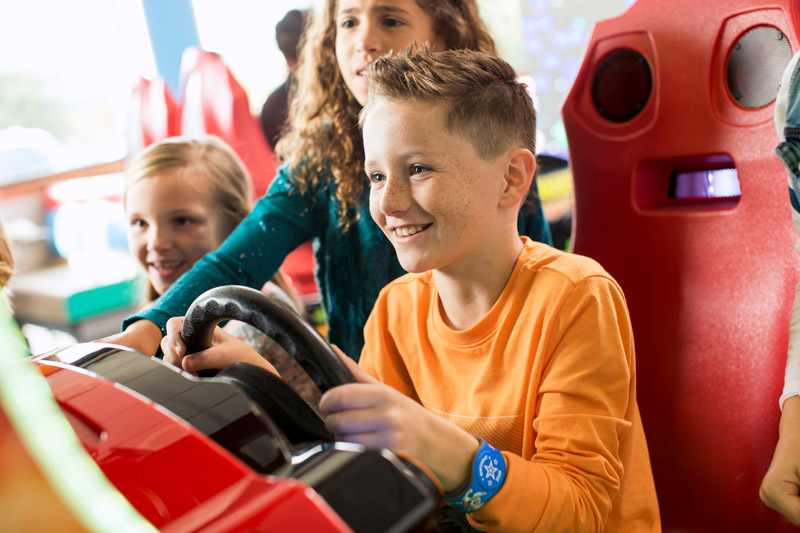 Child playing arcade racing game while two other children watch