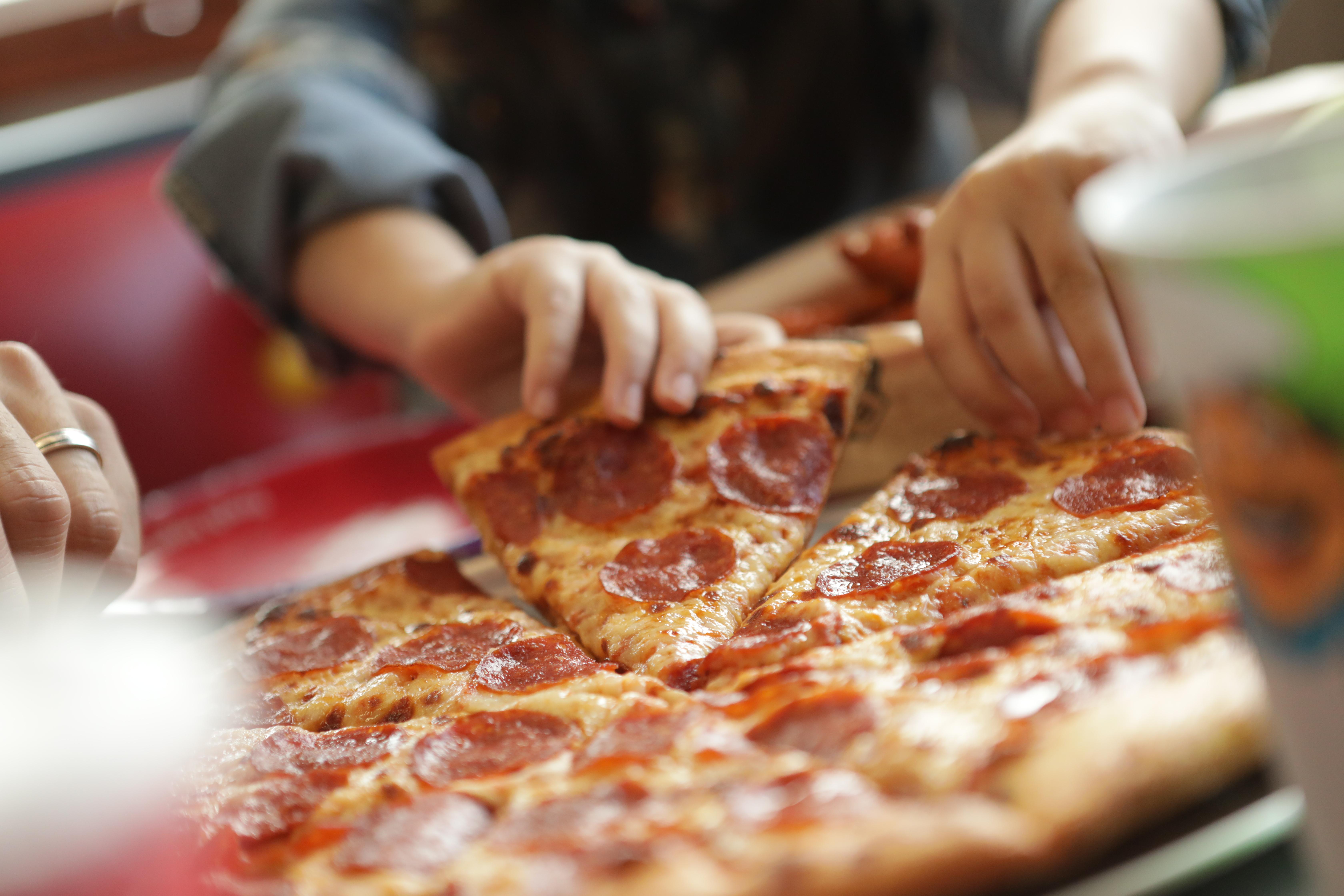 Hands grabbing pizza