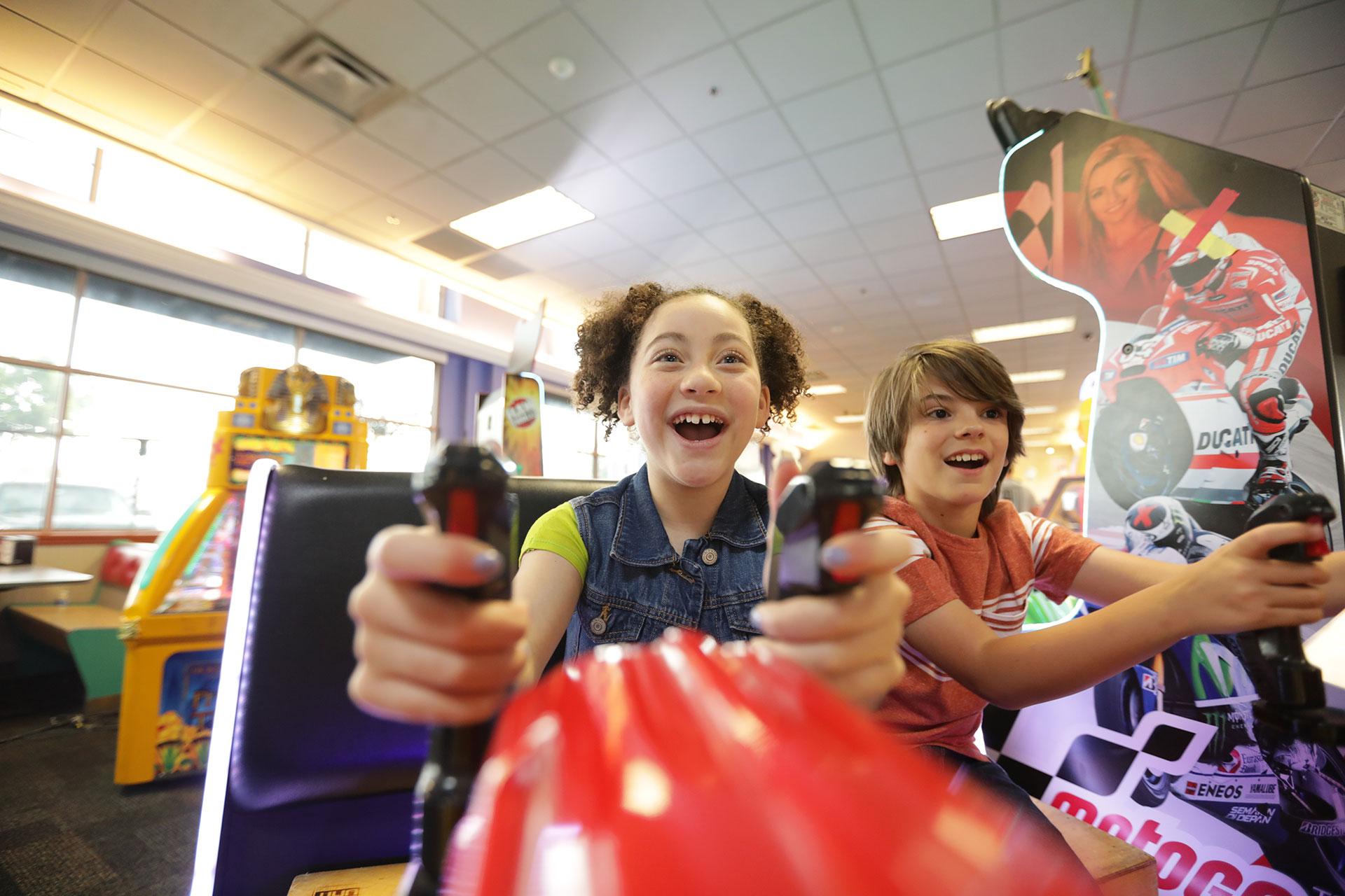 Two kids playing arcade game