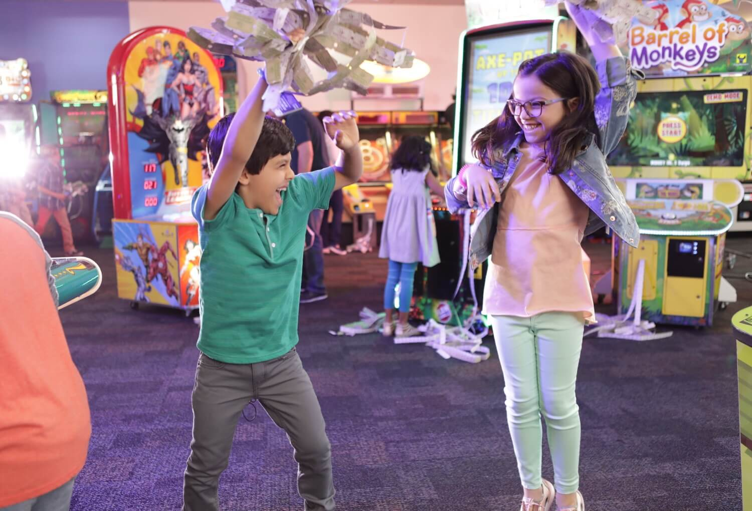 Two kids dancing while holding tickets