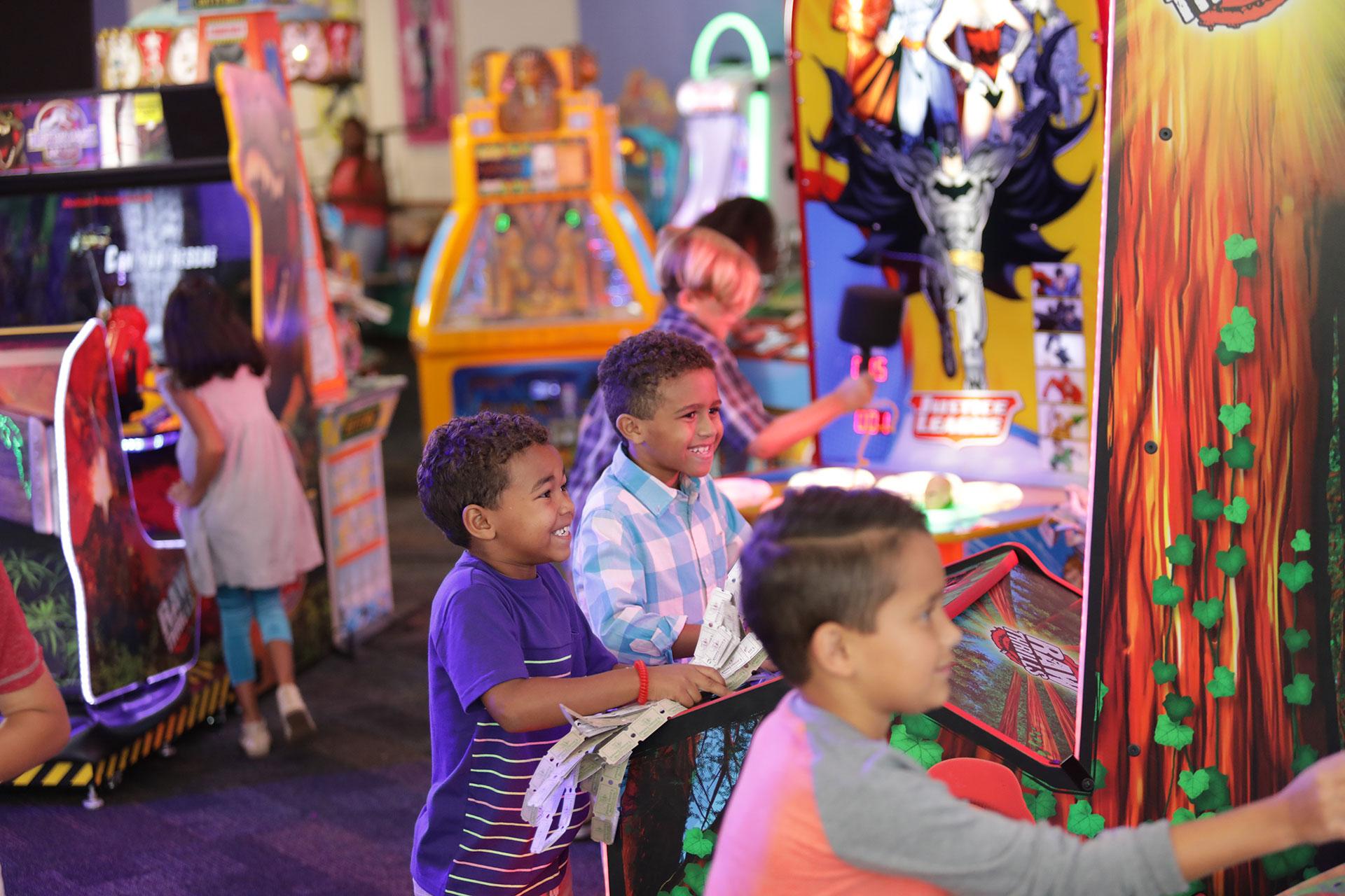 Three kids playing arcade game