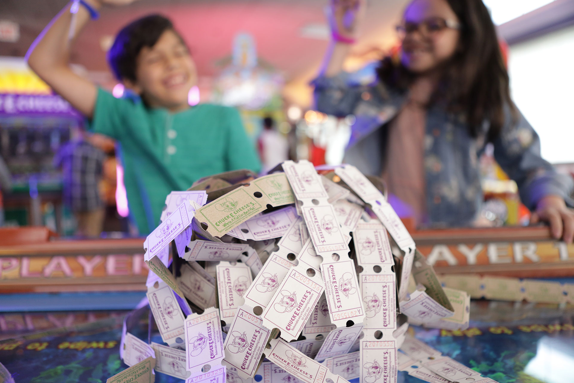 Two kids cheering behind pile of tickets